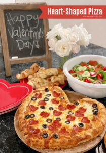 Valentine's Day dinner spread with a heart-shaped pizza