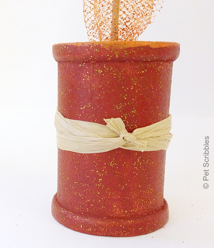 wooden spool tied with raffia ribbon