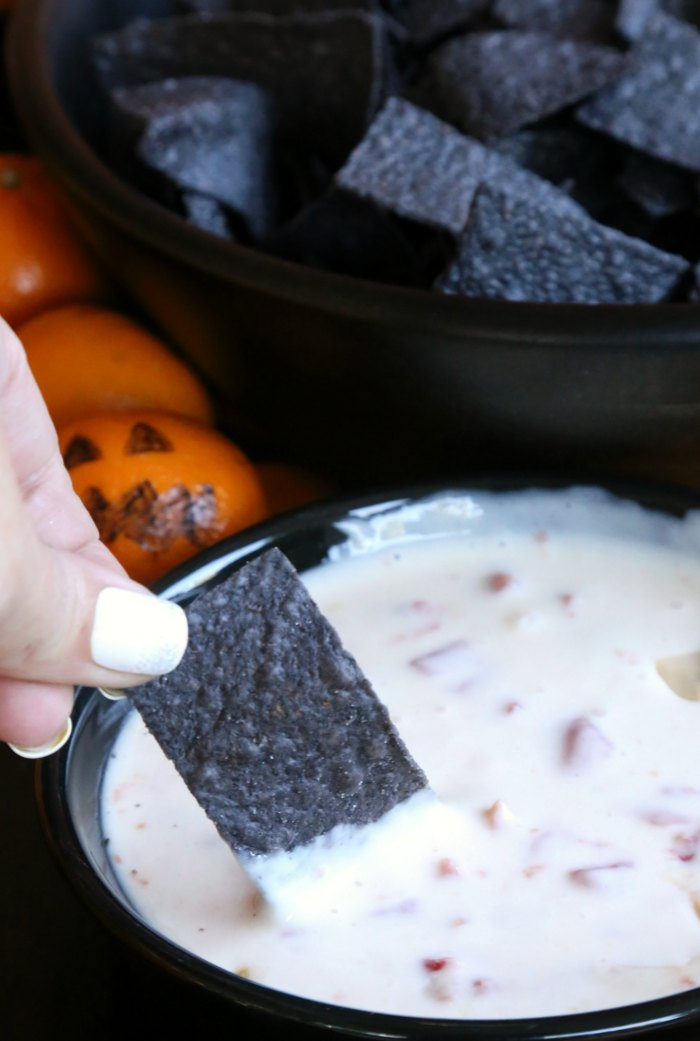 Black tortilla chip dipping in queso