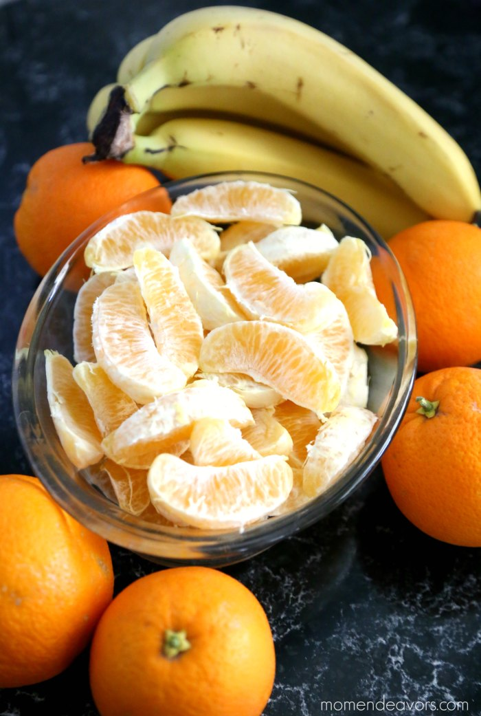Orange Slices in a dish with whole oranges and bananas