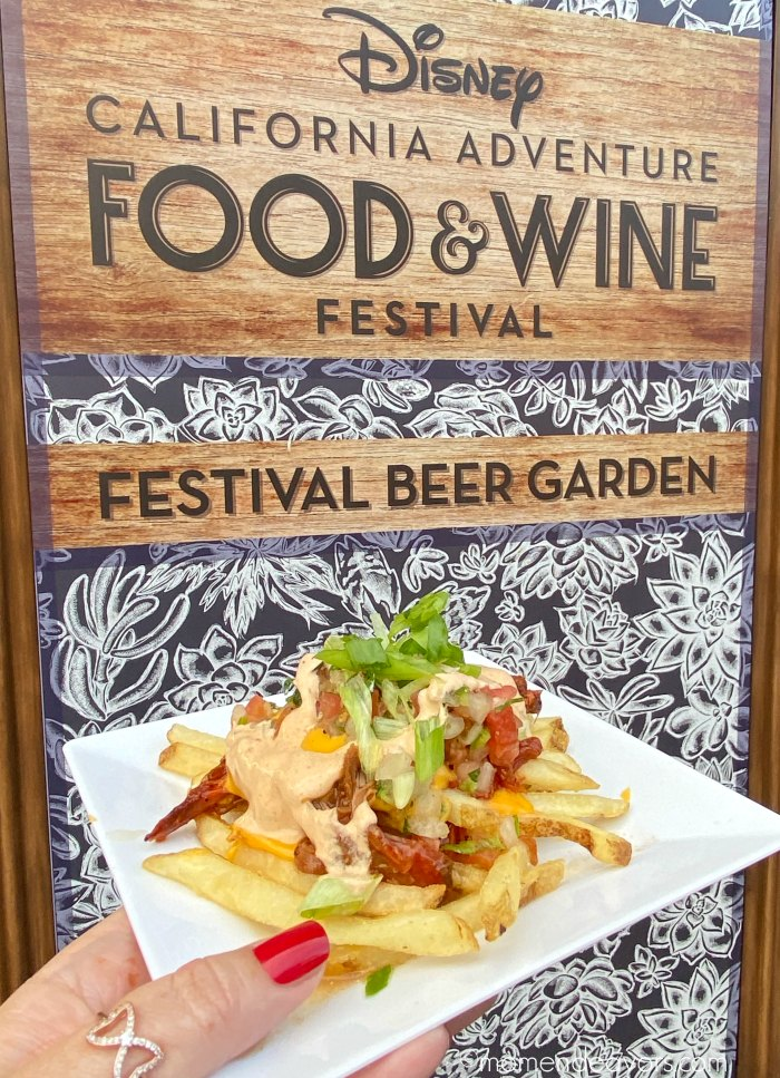 A plate of brisket fries in front of a Disney Food & Wine Festival Sign