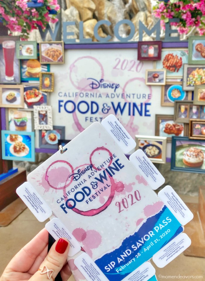 Disney Sip & Savor Pass in front of Food & Wine Festival Sign