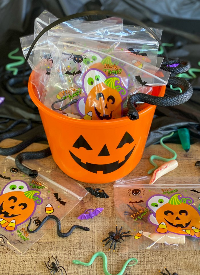 A pumpkin bucket filled with little Halloween items