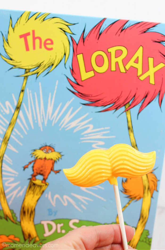 Lorax candy mustache held up in front of the book The Lorax