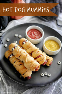 Mummy hot dogs on a plate with dip bowls of ketchup and mustard